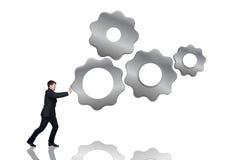 Kugghjul för affärsmanpushesmetall Arkivbilder