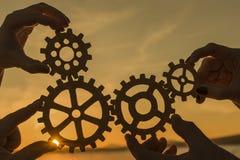 Kugghjul i händerna av ett lag av folk mot solnedgången arkivbilder