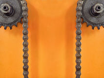 Kugghjul och dubbel kedja på orange bakgrund med tomt utrymme Arkivfoton