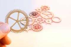 Kugghjulet rullar i hand på vit bakgrund som begrepp av teknik arkivfoto