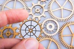 Kugghjulet rullar i hand p? vit bakgrund som begrepp av teknik fotografering för bildbyråer