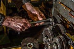 Kugghjulmetallhjul med arbetarhänder i industriell maskinnärbild royaltyfria bilder