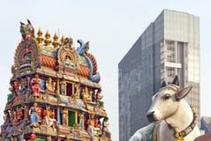 Kuh, hinduistischer Tempel und Wolkenkratzer lizenzfreie stockbilder