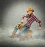 Kuhjunge, der ein gefälschtes Kinderpferd reitet Stockfotos