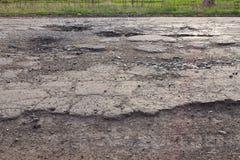 Kuilen en potholes op asfaltweg stock fotografie