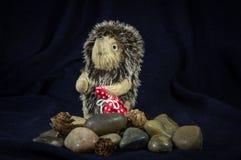 Kukiełkowy jeż z torbą na kamieniach Fotografia Stock