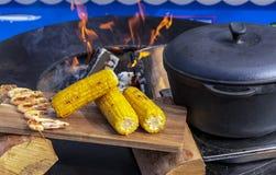 Kukurudzy, garneli i żeliwa kocioł obok round, piec na grillu obraz royalty free