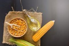 Kukurydzani nasiona i Kukurydzany olej w butelce na czarnym drewnianym tle Zdjęcia Royalty Free