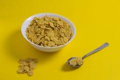 Kukurydzani płatki w talerzu na żółtym tła zbożu obraz royalty free