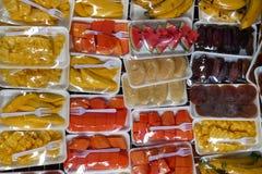Kulör bakgrund med frukter som slås in i cellofan med den vita plast- gaffeln Royaltyfria Bilder