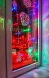 Kulör elektrisk girland i fönstret royaltyfri fotografi