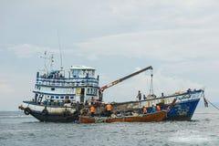 Kulör fiskebåt nära pir och ett litet träfartyg Stora gröna berg och andra fartyg är på bakgrunden Arkivbilder