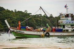 Kulör fiskebåt nära pir och ett litet träfartyg Stora gröna berg och andra fartyg är på bakgrunden Royaltyfri Fotografi