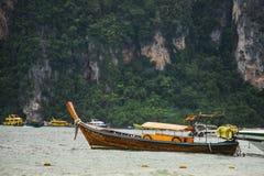 Kulör fiskebåt nära pir och ett litet träfartyg Stora gröna berg och andra fartyg är på bakgrunden Arkivfoto