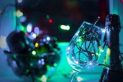 Kulör girland i ett exponeringsglas av champagne i natten Windows i julen för körning upp till royaltyfria foton