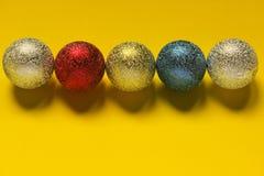Kulör julgarneringboll på en gul bakgrund med utrymme för text Arkivbild