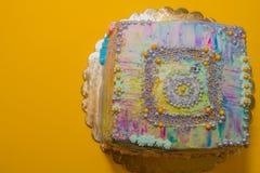 Kulör kaka på en gul bakgrund arkivfoton