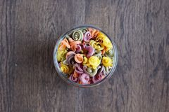 Kulör pasta i kan på trätabellen fotografering för bildbyråer