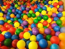 Kulör plast- klumpa ihop sig i pöl av modigt rum Simbassäng för gyckel och banhoppning i kulöra plast- bollar arkivfoton