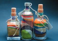 Kulör sand hällde in lager i en flaska arkivfoto