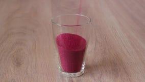 Kulör sand hälls in i exponeringsglaset och snäckskalen som överst förläggas stock video