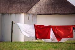 Kulör torkduk som hänger på en klädstreck mot vita radhus med halmtäckte tak Royaltyfri Bild