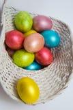 Kulöra ägg för påsk i en vit korg Arkivfoto