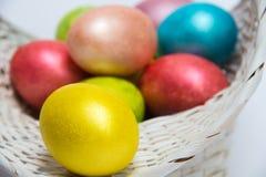 Kulöra ägg för påsk i en vit korg Arkivbilder