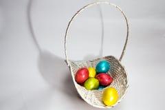 Kulöra ägg för påsk i en vit korg Royaltyfria Foton