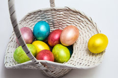 Kulöra ägg för påsk i en vit korg Fotografering för Bildbyråer