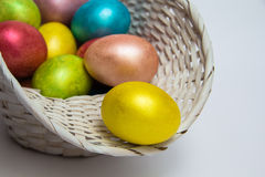 Kulöra ägg för påsk i en vit korg Royaltyfria Bilder