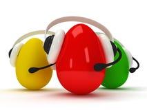 Kulöra ägg med hörlurar med mikrofon över vit Arkivbild