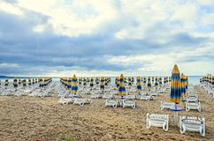 Kulöra avrivna solparaplyer, guld- strandsand och sunbeds Royaltyfri Foto