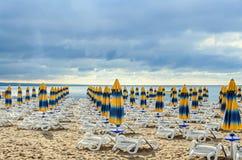 Kulöra avrivna solparaplyer, guld- strandsand och sunbeds Royaltyfria Bilder