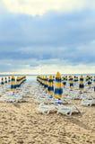 Kulöra avrivna solparaplyer, guld- strandsand och sunbeds, s Arkivfoto