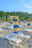 Kulöra avrivna solparaplyer, strandsand och sängar Royaltyfri Fotografi