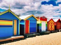 Kulöra badningaskar på den Brighton stranden Arkivbild