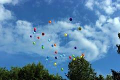 Kulöra ballonger som flyger bort in i himlen fotografering för bildbyråer