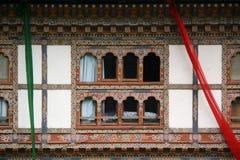 Kulöra baner hängdes på fasaden av ett hus i Lobesa (Bhutan) arkivfoto