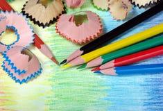 kulöra blyertspennashavings blyertspennor på en regnbågebakgrund Färger av regnbågen royaltyfria foton