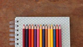 Kulöra blyertspennor är på anteckningsboken Royaltyfri Bild
