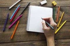 Kulöra blyertspennor, anteckningsbok och hand Royaltyfri Fotografi