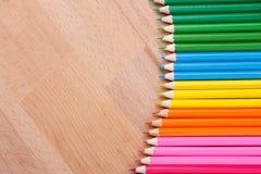 Kulöra blyertspennor färgade blyertspennor på trätabellclousen-up Fotografering för Bildbyråer