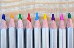 Kulöra blyertspennor färgade blyertspennor på trätabellen Arkivbilder