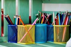 Kulöra blyertspennor i en kopphållare arkivfoto