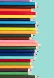 Kulöra blyertspennor i en ordning på en vit bakgrund royaltyfri fotografi