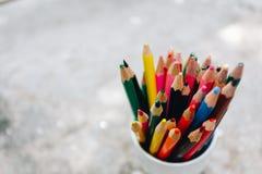 Kulöra blyertspennor i ett exponeringsglas på bakgrund arkivfoton