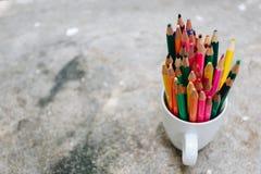 Kulöra blyertspennor i ett exponeringsglas på bakgrund arkivbild