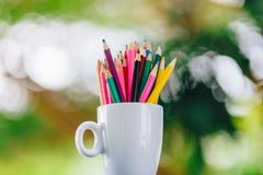 Kulöra blyertspennor i ett exponeringsglas på Bokeh bakgrund royaltyfria foton