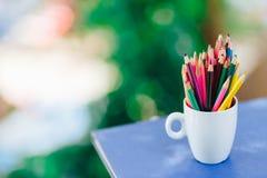 Kulöra blyertspennor i ett exponeringsglas på Bokeh bakgrund royaltyfri fotografi